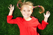 Little girl smiling on grass — ストック写真