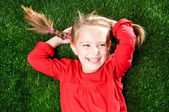 Little girl smiling on grass — Stock Photo