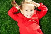 Dziewczynka uśmiechając się na trawie — Zdjęcie stockowe