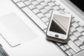 Modern communications concept. White communicator on silver lapt — Stock Photo