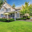 Large beige house with green grass - Stock Photo