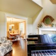 图库照片: Cream yellow living room with grand piano and dining