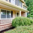 Large beige house with covered front porch — Zdjęcie stockowe #7589489