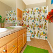 Stock Photo: Bathroom with green rug, double sinks and bright shower curtain