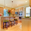 Stock Photo: Large luxury maple wood kitchen with island and stools