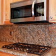 Kitchen microwave and stove top with granite background — Stock Photo #7590854