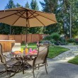 Backyard with table and unbrella — Stock Photo