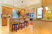 Large luxury maple wood kitchen with island and stools — 图库照片