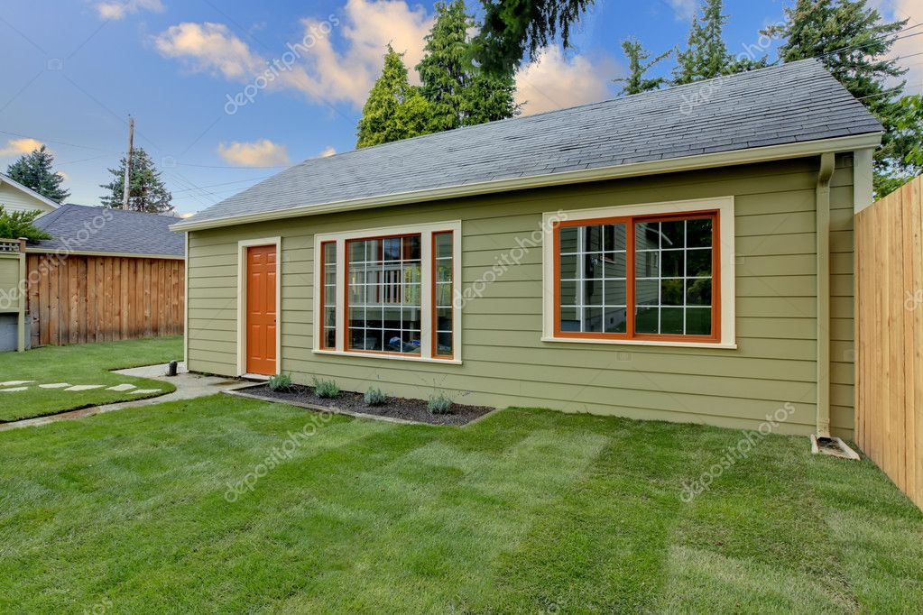 Small green guest house in the fenced backyard stock for Backyard little house