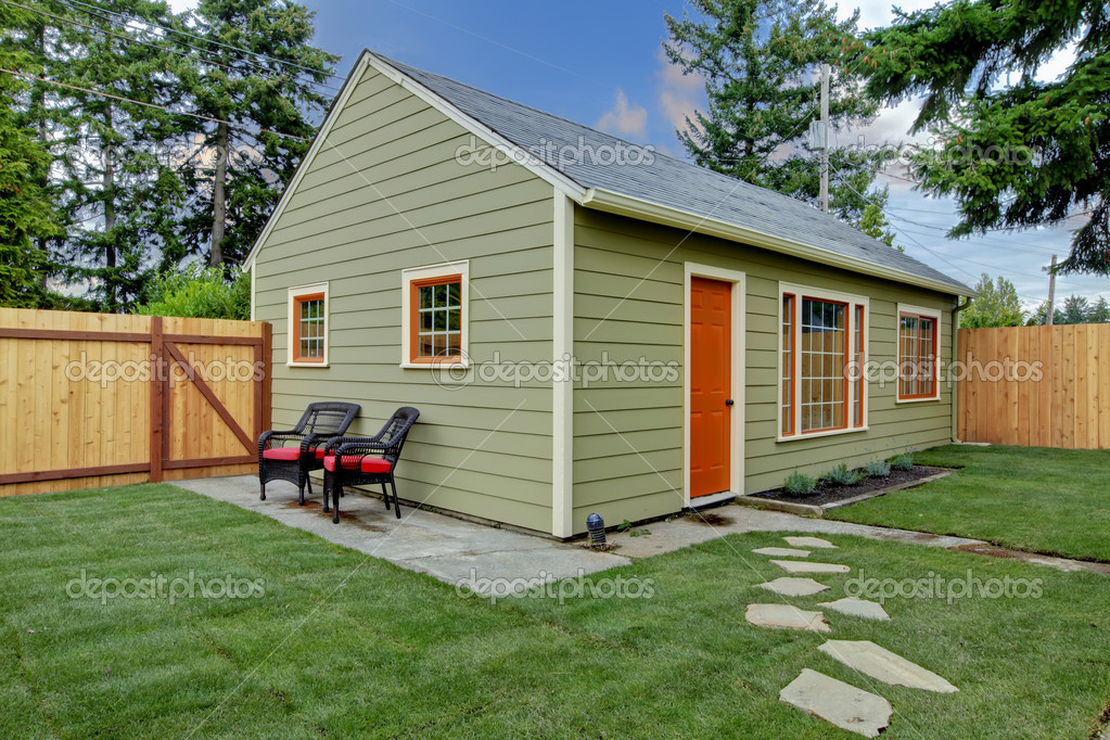 Small green and orange guest house in the back yard Tiny house in backyard