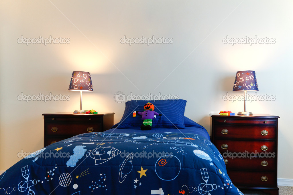 blue boys bed with two lamps in a white bedroom stock photo