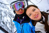 Young couple on the chair lift at the skiing resort. — Stock Photo