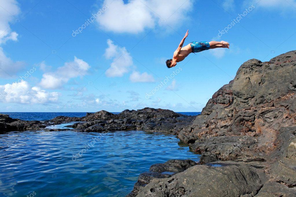 Jovem homem pulando do penhasco em que a gua for 7 piscinas sagradas maui