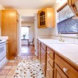 Oak cabinets kitchen with tile floor and flowers — Stock Photo