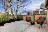 Deck with two chairs and fenced yard near home exterior shot. — Foto de Stock