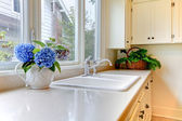 Kitchen sink with white cabinets and flowers. — Stock Photo