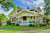 Green old craftsman style home with covered porch. — Stock Photo