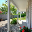 Deck with a covered part and fenced yard. — Stock Photo