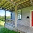 Stock Photo: Small covered porch with red door.