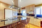Nova cozinha de luxo com luz cbainets e ilha escura. — Foto Stock
