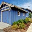 Detached garage of Blue house from the back yard. - Stock Photo
