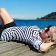 Blond beautiful girl near the sea in a stripe T-shirt. — Stock Photo #7899192