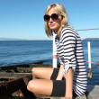 Blond beautiful girl near the sea in a stripe T-shirt. — Stock Photo #7899195