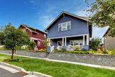 Casa azul con muro de piedra y porche cubierto. — Foto de Stock