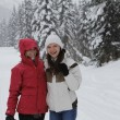 Two young laughing happy women in the snow forest — ストック写真