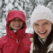 Two young laughing happy women in the snow forest — Stock Photo