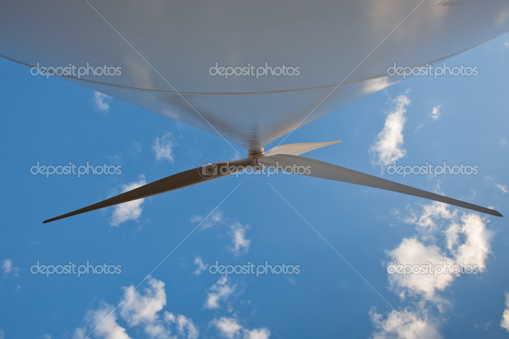 Three enormous blades attached to a giant windmill slowly rotate overhead against a blue sky with small white clouds. — Stock Photo #6987501