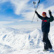 Stock Photo: Cheerful skier on the top of mountain