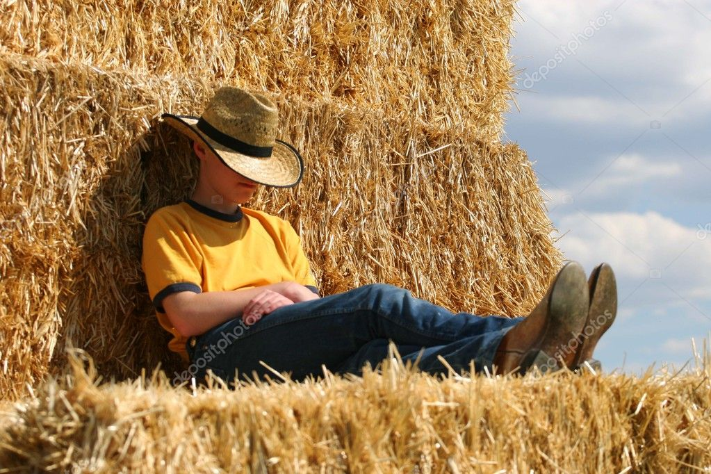 Male cowboy sleeping in straw stack with cowboy hat pulled over face wearing yellow shirt and blue jeans in the sun  Stock Photo #6821533