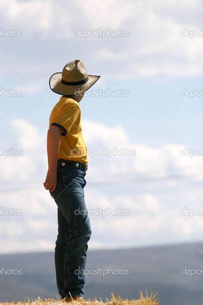 Male cowboy standing on straw stack looking off into distance wearing yellow shirt and blue jeans with cowboy hat — Photo #6821600