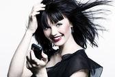 Schönes mädchen mit roten lippenstift, perfekte haut und schwarze haare mit telefon — Stockfoto