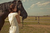 Beautiful girl in a white gown with horse on nature — Stock Photo