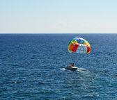 Colored parachute over a sea — Stock Photo