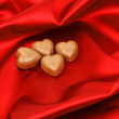 Candy hearts on red satin — Stock Photo