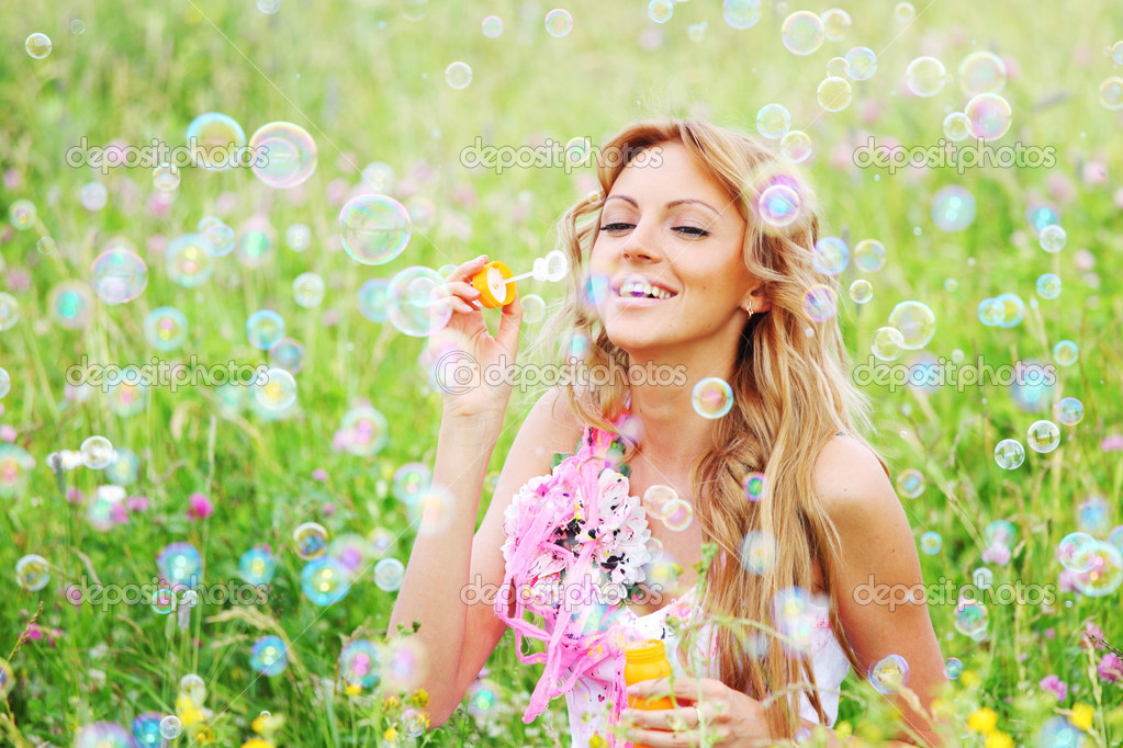 Blonde starts soap bubbles in a green field — Stock Photo #6752941