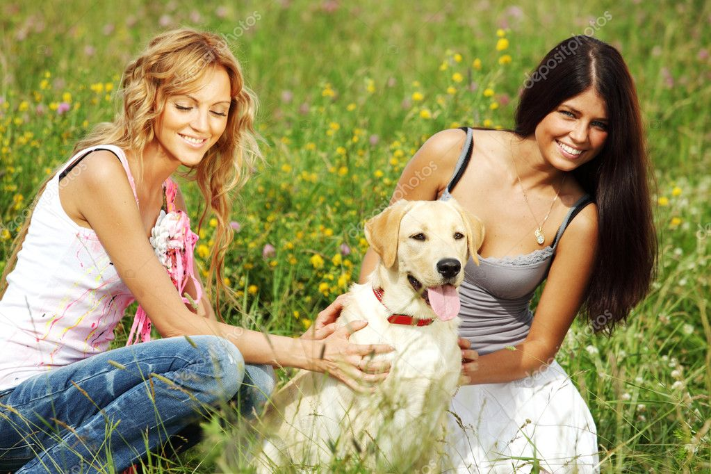 Girlfriends and dog in green grass field — Stock Photo #6848455