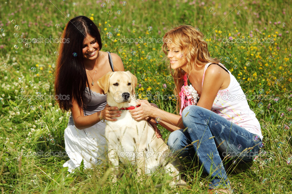 Girlfriends and dog in green grass field — Stock Photo #6848468
