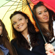 Smiling girlfriends under umbrella — Stock Photo