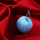 Thread on red silk — Stock Photo