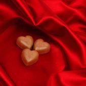 Serca cukierków na czerwono satyna — Zdjęcie stockowe