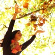 Stock Photo: Woman drop leaves in autumn park