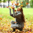 Woman drop leaves in autumn park — Stock Photo #6934443