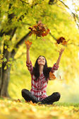 Woman drop leaves in autumn park — Стоковое фото
