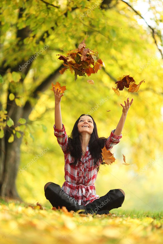 Woman drop up leaves in autumn park — Stok fotoğraf #6933709