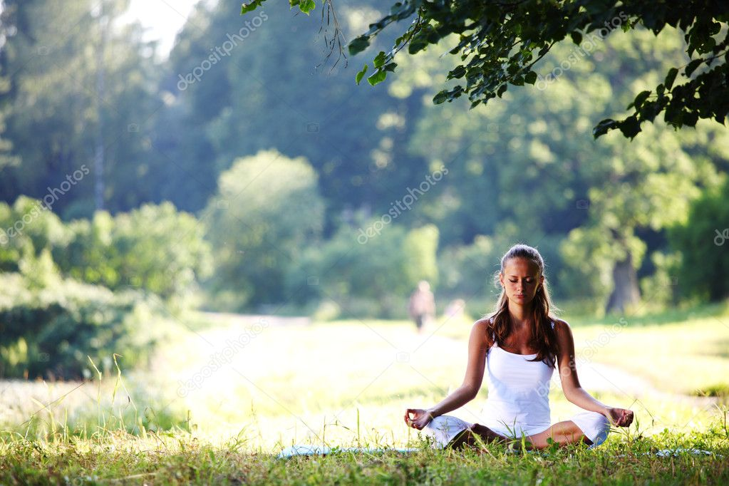 Yoga woman on green grass in lotus pose  Stock Photo #6933913