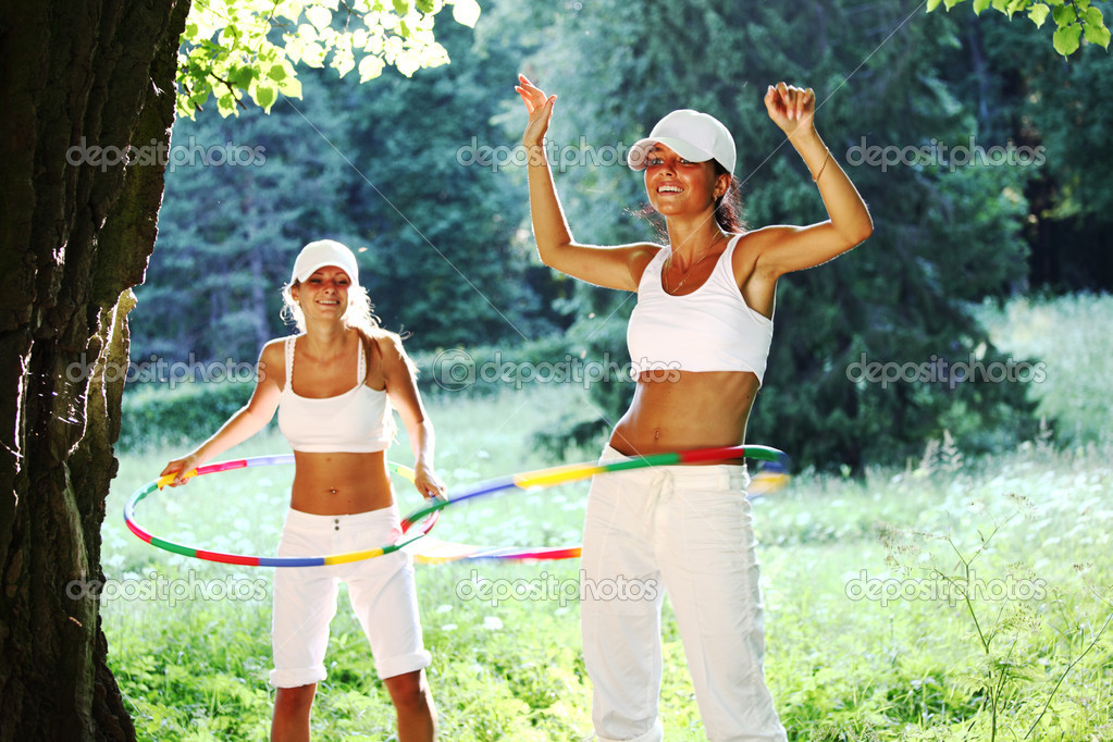 Woman rotates hula hoop on nature background — Stock Photo #6934346